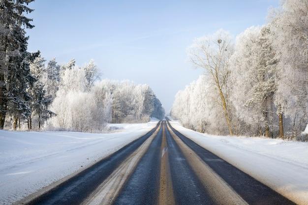 Gevaarlijke snelheidsadviezen wegen in het winterseizoen, zonnig weer, de bomen zijn bedekt met veel witte sneeuw.
