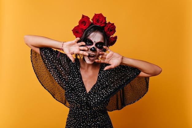 Gevaarlijke vrouw met schedelmasker probeert bang te maken. foto van meisje met rozen in haar haar op oranje achtergrond.