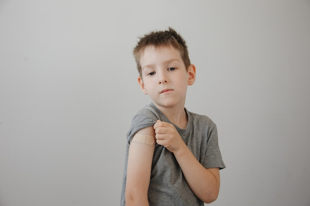 Gevaccineerde jongen toont arm na covid-19 vaccininjectie