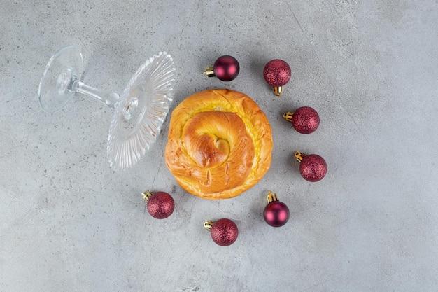 Gevallen glazen voetstuk, halve cirkel van kerstboomdecor en zoet broodje op marmeren oppervlak