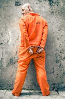 Gevangene met handboeien bij gevangenismuur
