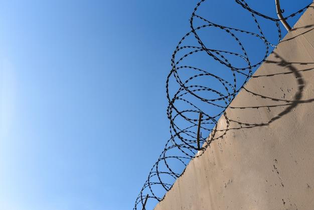 Gevangenismuur met prikkeldraad tegen de blauwe hemel