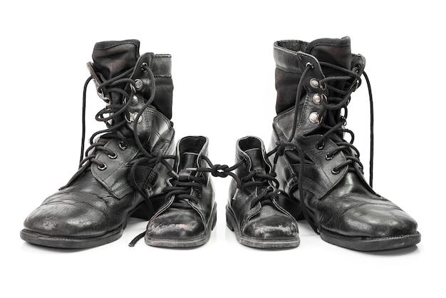 Gevechtslaarzen voor volwassene en kind in familieconcept dat op wit wordt geïsoleerd