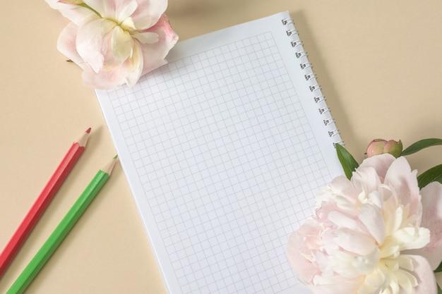 Geveerd notitieboekje en kleurpotloden, grote beige bloemen en pioenrozen op een beige achtergrond. bovenaanzicht. ruimte kopiëren.