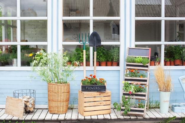 Gevel huis met tuingereedschap en potten bloemen veranda van huis met groene planten en bloemen