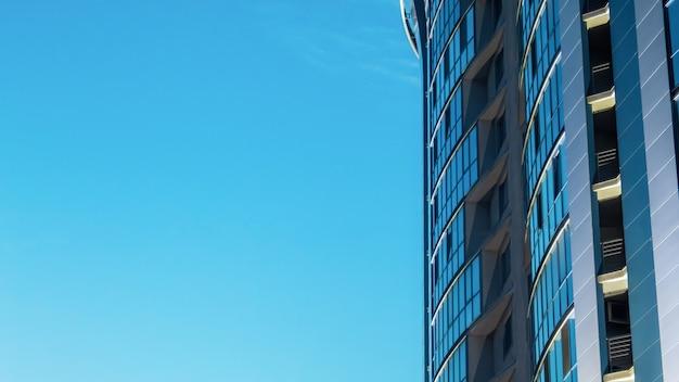 Gevel van een modern gebouw gemaakt van metaal en glas met blauwe heldere hemel