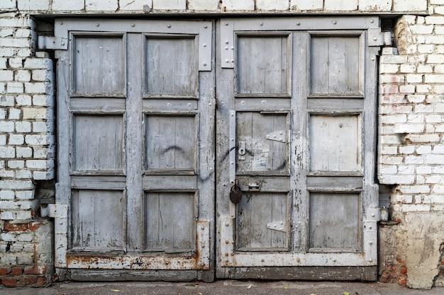 Gevel van een verlaten gebouw. ouderwetse voordeur in vuilwitte en grijze kleur.