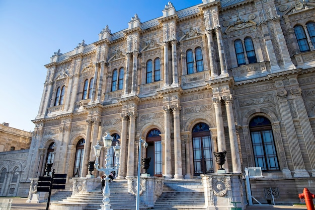 Gevel van het dolmabahçepaleis met mensen op de trappen ervoor in istanboel, turkije