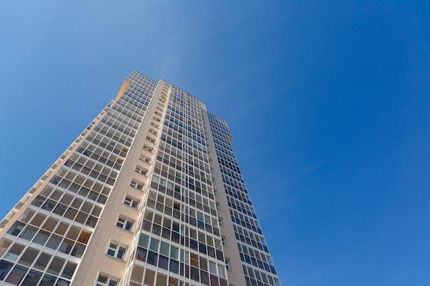 Gevel van nieuw hoog gebouw tegen blauwe hemel