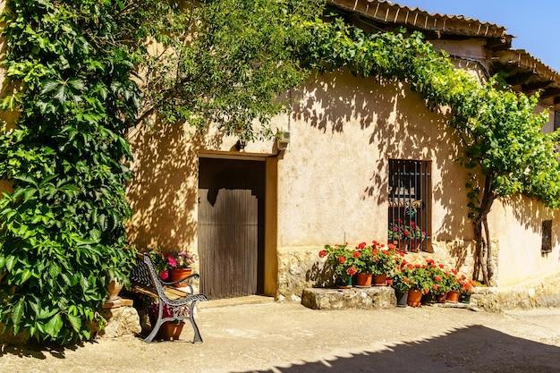 Gevel van oud landhuis met zitbank bij de ingang en groene planten.