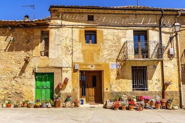 Gevel van oud stenen huis met bloempotten bij de ingang.