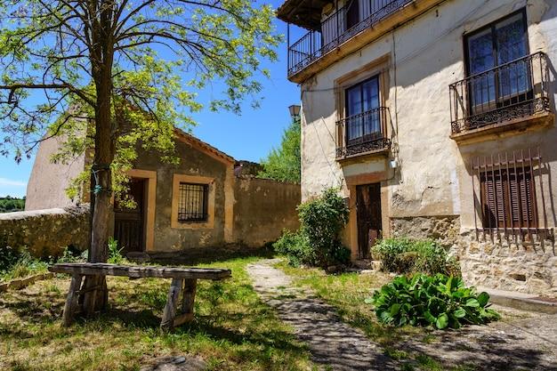 Gevel van oude huizen met kleine tuin met oude houten bank