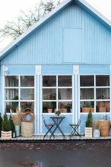 Gevel woning met rieten manden, houten tafel en stoelen op veranda
