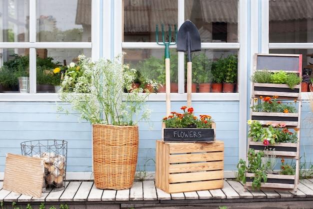 Gevelhuis met tuingereedschap rieten mand en potten bloemen interieur zomer veranda huis