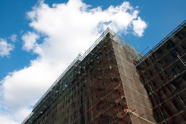 Gevelrenovatie van het gebouw over blauwe lucht, wederopbouw van het oude huis, reparatie. steiger voor de gevel van het gebouw bedekt met transparante stof