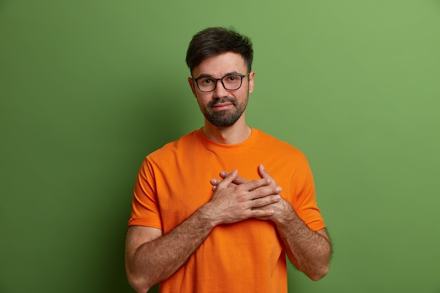 Gevleid blij ongeschoren man drukt handen naar het hart, drukt hartverwarmende gevoelens uit en dankbaarheid waardeert lof draagt transparante bril en fel oranje t-shirt geïsoleerd op groene muur