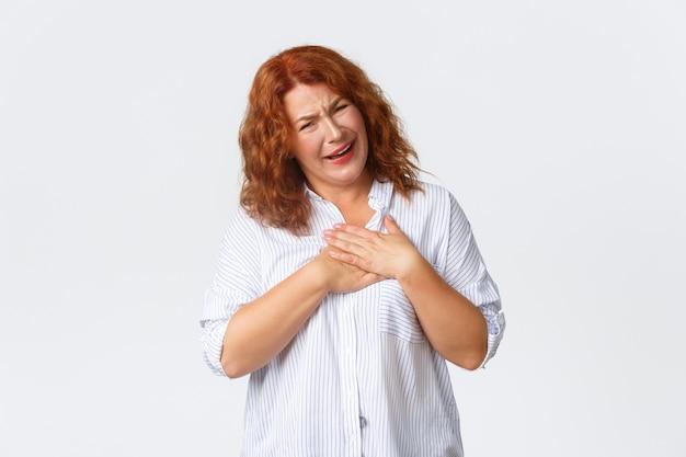 Gevleid en opgetogen gelukkig roodharige vrouw van middelbare leeftijd hand in hand op het hart, zuchtend en kijkend met een schattige uitdrukking, geprezen worden, een compliment ontvangen of aangeraakt worden, witte muur.
