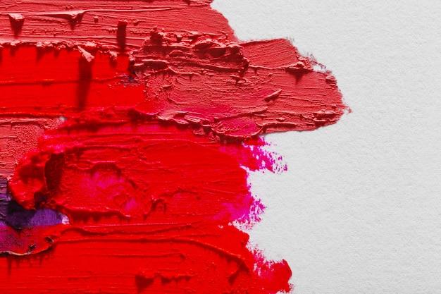Gevlekte kleurrijke lippenstift op wit, close-up