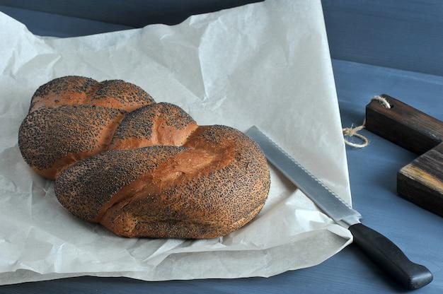Gevlochten brood met maanzaad op bruin papier met een broodmes