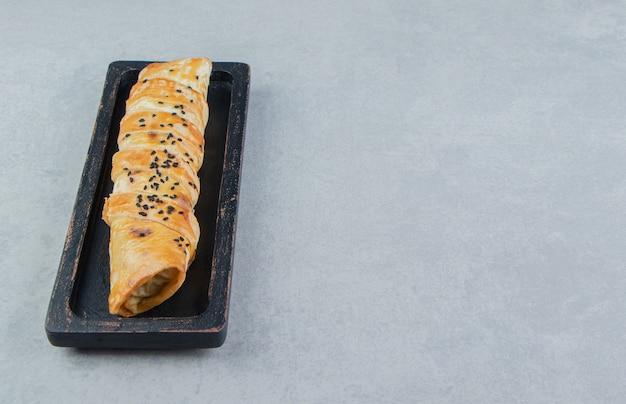 Gevlochten broodje gevuld met vlees op zwarte plaat.