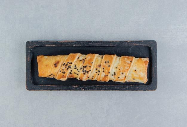 Gevlochten broodje met sesamzaadjes op zwarte plaat. Gratis Foto