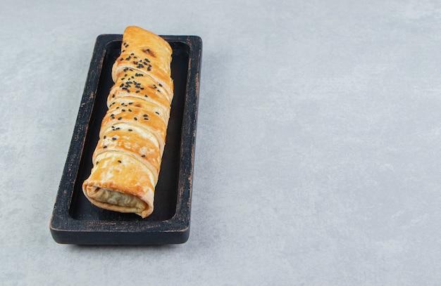 Gevlochten broodje met sesamzaadjes op zwarte plaat.