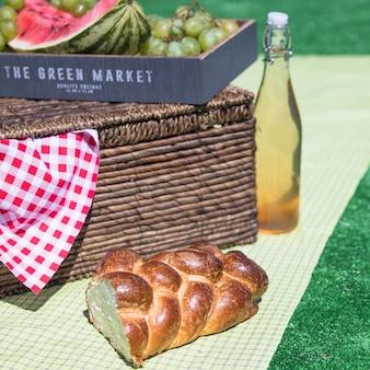 Gevlochten gebakken brood; vers fruit en een picknickmand op doek