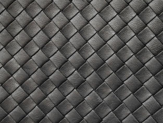 Gevlochten textuur van oud zwart leer.