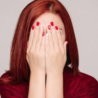 Gevoede haired onherkenbare vrouw die warm grijs seater verbergend gezicht door handen draagt.
