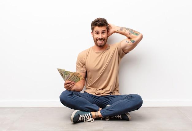 Gevoel gestrest, bezorgd, angstig of bang, met de handen op het hoofd, in paniek bij het vasthouden van dollarbiljetten