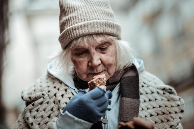 Gevoel van honger. aardige oude vrouw die naar het brood kijkt terwijl ze het wil eten