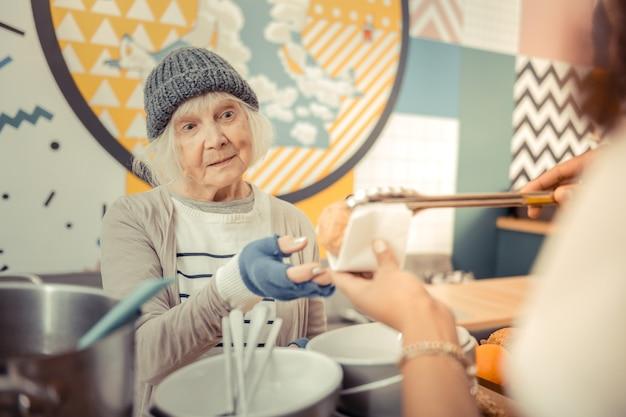 Gevoel van honger. arme dakloze vrouw die naar het eten kijkt terwijl ze wil eten