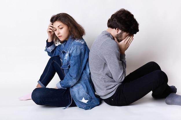 Gevoelens en attitudes. een paar zittend op de vloer steunt moe en verdrietig expressie na een kleine ruzie
