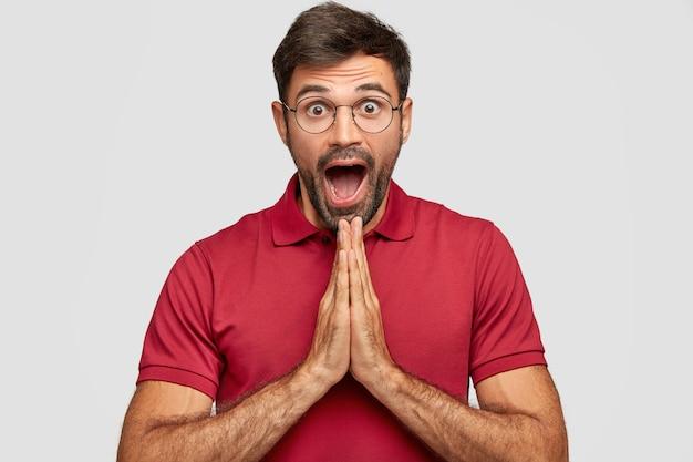 Gevoelig geschokt mannetje houdt handen in gebed, kan niet geloven dat zijn dromen zo snel uitkomen, gekleed in vrijetijdskleding, staart door een bril, geïsoleerd over een witte muur. omg, god sta me bij!