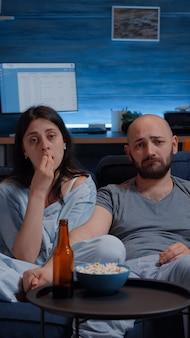 Gevoelig paar kijken naar dramafilm op tv huilend zittend op de bank popcorn etend 's avonds laat