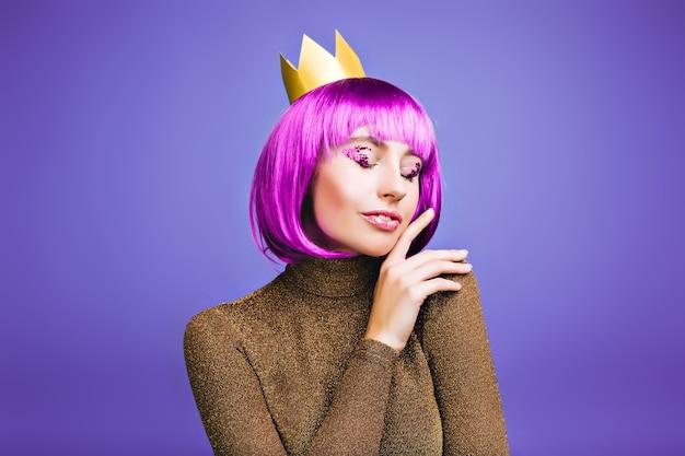 Gevoelig stijlvol portret van modieuze vrolijke jonge vrouw carnaval vieren in gouden kroon op violette ruimte.