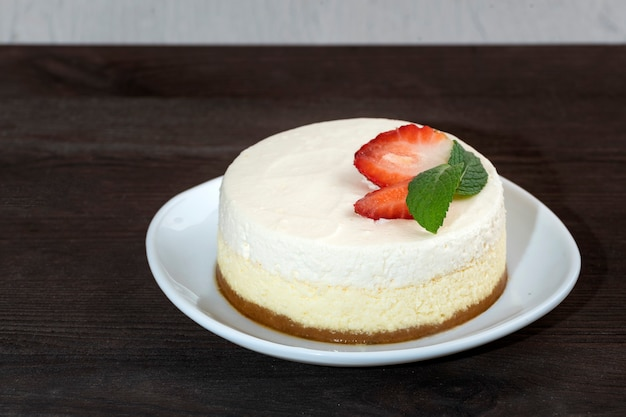 Gevoelige cheesecake-cake met verse aardbeien en munt op witte plaat op houten achtergrond hoogste mening