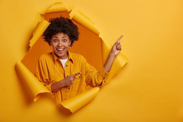 Gevoelige donkere vrolijke vrouw wijst naar de rechterbovenhoek, geeft instructies en maakt reclame voor kopie ruimte