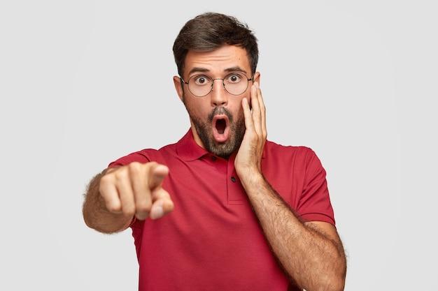 Gevoelige doodsbange blanke man met opengevallen kaak, merkt iets vreselijks op straat, wijst met wijsvinger in de verte, gekleed in een rood t-shirt, geïsoleerd op een witte muur. reactie concept