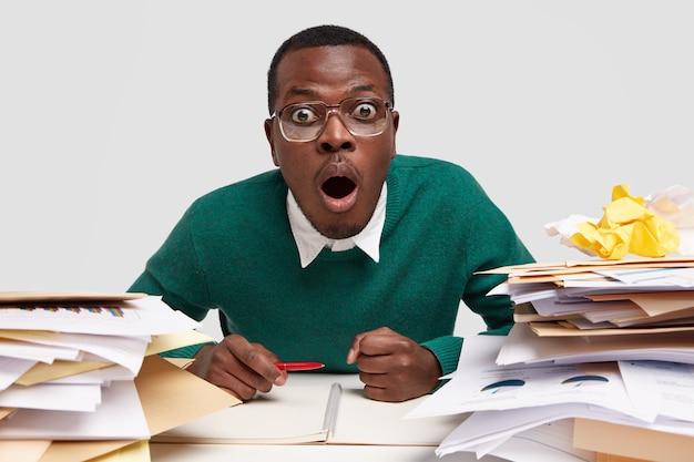 Gevoelige geschokte geïrriteerde mannelijke student houdt vuist op desktop, opent mond wijd, staart door bril, werkt aan projecten en schrijft lijst om te doen