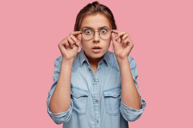 Gevoelige jonge blanke vrouw staart hoewel grote brillen