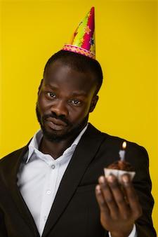 Gevoelige knappe afrikaanse man met een verjaardagstaart.