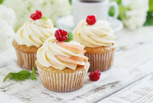 Gevoelige vanille cupcakes met room en frambozen op een witte houten tafel