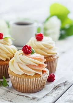 Gevoelige vanille cupcakes met room en frambozen op witte houten