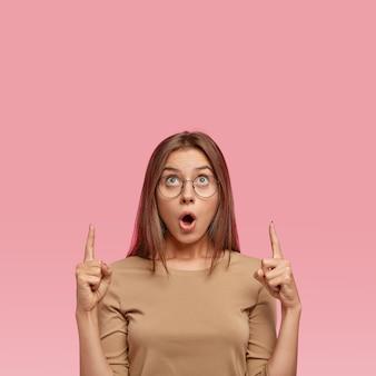 Gevoelige, verbijsterde europese vrouw wijst met beide wijsvingers naar boven