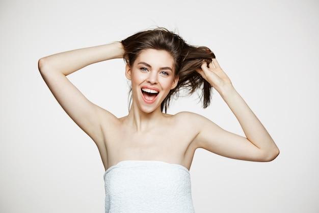 Gevoelige vrolijke jonge vrouw die verheugend wat betreft haar glimlachen. spa schoonheid en huidverzorging.