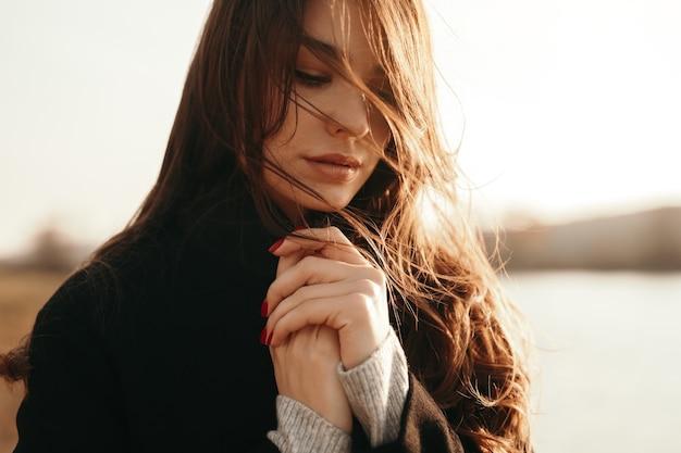 Gevoelige vrouw die zich dichtbij meer in de herfst bevindt