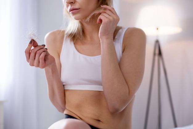 Gevolgen van anorexia. depressieve, ongelukkige vrouw die naar het plukje haar kijkt terwijl ze aan anorexia lijdt