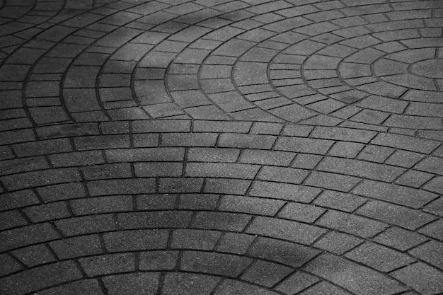 Gevormde straatstenen, de oude vloer van de cementbaksteen - zwart-wit achtergrond