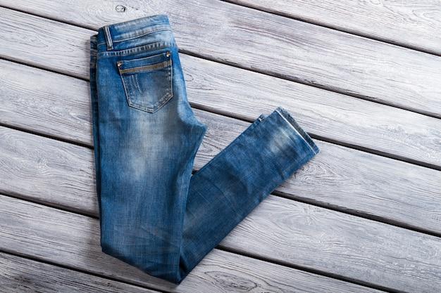 Gevouwen blauwe spijkerbroek. denim broek op houten achtergrond. nieuwe casual jeans voor dames. laatste item voor speciale prijs.